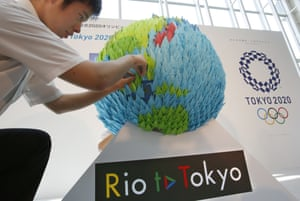 A man adjusts a display for a 2020 Tokyo Olympic countdown event at Haneda airport in Tokyo, Sunday, July 24, 2016. The giant globe is made from 2,020 origami paper cranes. (AP Photo/Shizuo Kambayashi)
