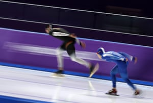 Germany's Moritz Geisreiter and South Korea's Lee Seung-hoon compete during the men's 10,000m speedskating.