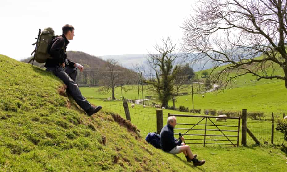 Grandfather and grandson walkers resting in lush green landscape