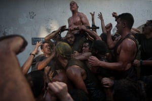 People covered in grease climb on each other during the festival of the Cascamorras