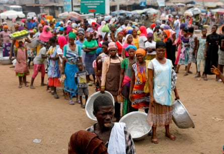 People wait to receive food and water from volunteers in Accra during the partial lockdown on 4 April.