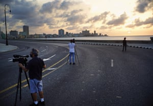 Members of the media film the empty Malecón esplanade