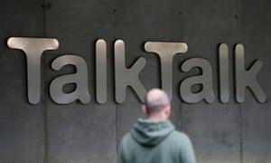 A man walks past a company logo outside a TalkTalk building in London.
