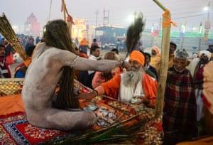 A devotee seeks blessings from a Naga Sadhu.