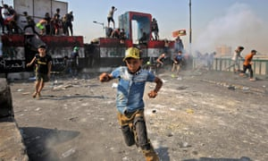 Anti-government protesters flee during clashes with riot police in Baghdad, Iraq