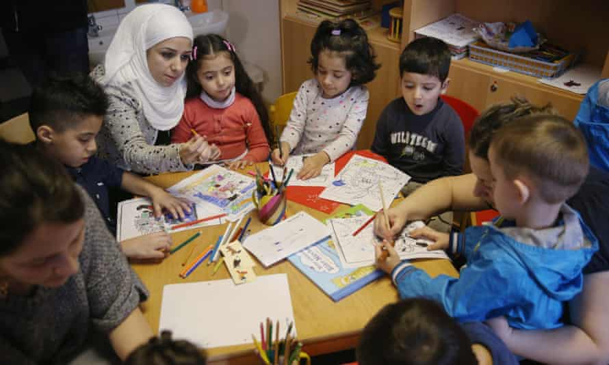 Refugee mothers and children look through games and books in another initiative by the German education ministry, the reading start for refugee children.