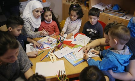 Immigrant mothers look through games and books with their children in Berlin, Germany, last year.
