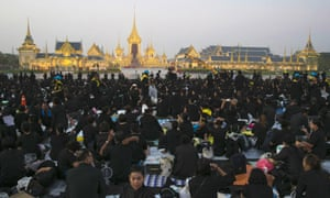 Thai mourners sit in front of the royal crematorium and funeral complex.