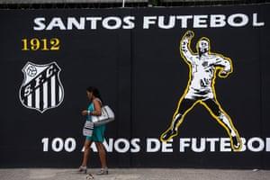 A woman walks past Santos's training facility.
