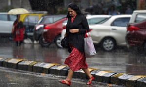A woman crosses a road as it rains in Mumbai, India,