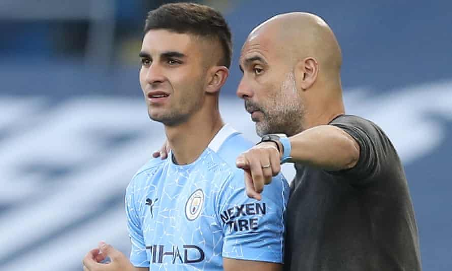 Manchester City's Ferran Torres takes instruction from Pep Guardiola