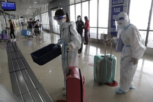 Passengers wearing protective suits push their bags as they prepare for their flight to China at Manila's International Airport, Philippines, on Monday, 18 January, 2021.