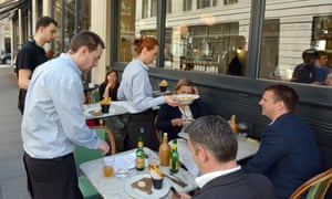 Waiters serving food and drinks to people dining in a restaurant in London England