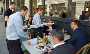 Waiters serve customers at a restaurant in London