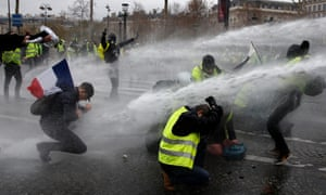 Gilets jaunes are sprayed with water cannon near the Arc de Triomphe. Photograph: Yoan Valat/EPA