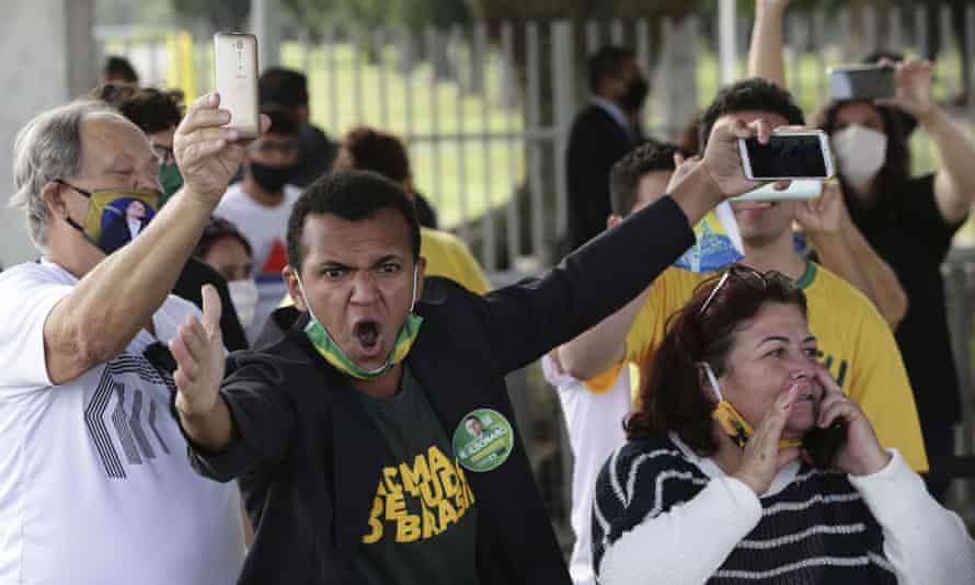 Supporters of Jair Bolsonaro hurl abuse at journalists outside the Palácio da Alvorada in Brasília on Monday.