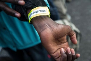 A Refugee shows wristband showing by colour which area of the country he will be sent to.