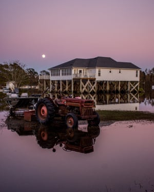 A home on stilts narrowly escapes the flood as the sun sets in Rocky Point.