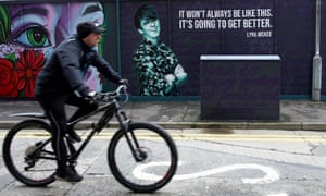 A man cycles past a mural featuring Lyra McKee in Belfast.
