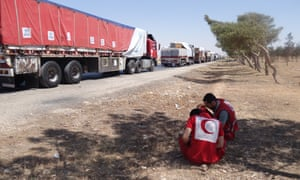 Two volunteers crouch next to a long line of aid trucks