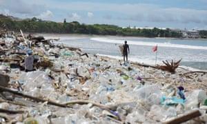 Um surfista está diante de montes de lixo na famosa Praia de Kuta em Bali