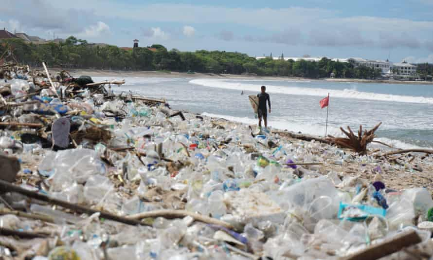 A surfer stands before mounds of garbage on Bali's famous Kuta Beach