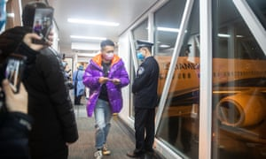 A Hubei province resident, disembarking a chartered Xiamen Airline plane, arrives at Wuhan Tianhe International Airport