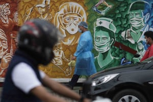 A man in a protective suit to prevent the spread of the coronavirus walks beside a mural of health workers outside the Mission Hospital in Pasig, Philippines, Monday, 22 February, 2021.