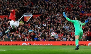 Marcus Rashford of Manchester United scores the opening goal past Liverpool goalkeeper Alisson.