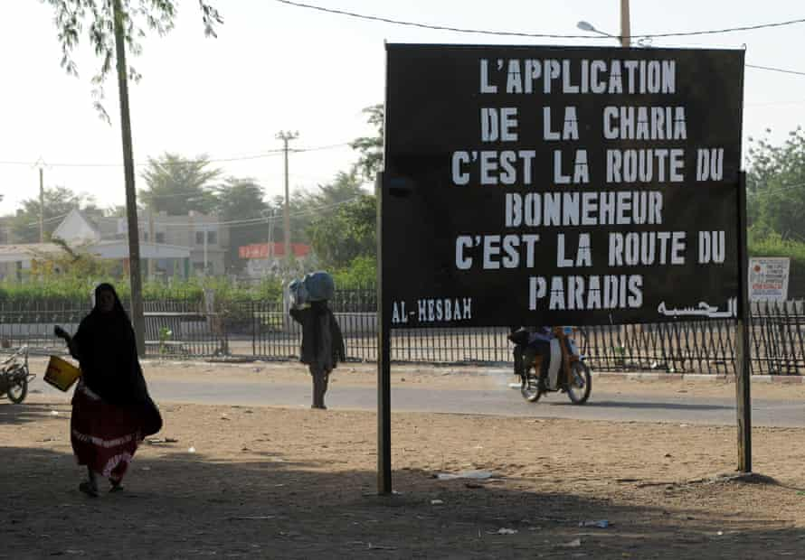 Malians walk past a billboard left by Islamic militant group MUJAO, which reads: 'Enforcing Sharia [law] is the road to happiness, it is the road to paradise,' in the northern city of Gao.