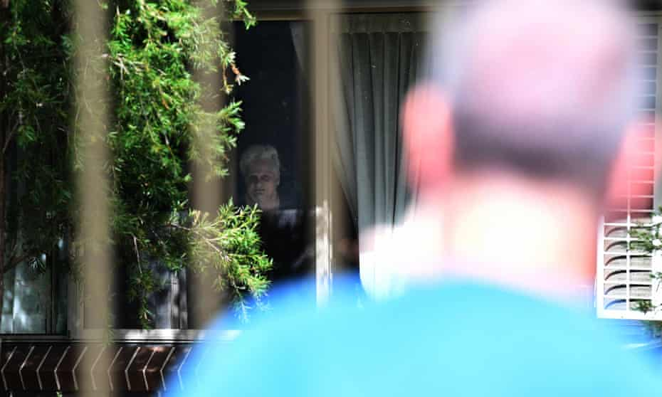 Anthony Bowe is seen by his mother Patricia Shea from outside the perimeter fence of the Newmarch House aged care home in Penrith, in Sydney's west.