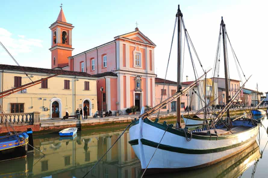 A boat in front a pink church in the port of Cesenatico (Italy)
