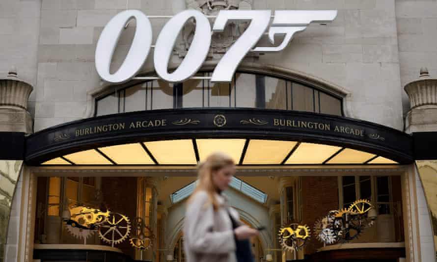 A pedestrian passes a James Bond 007 logo above the entrance to Burlington Arcade in London