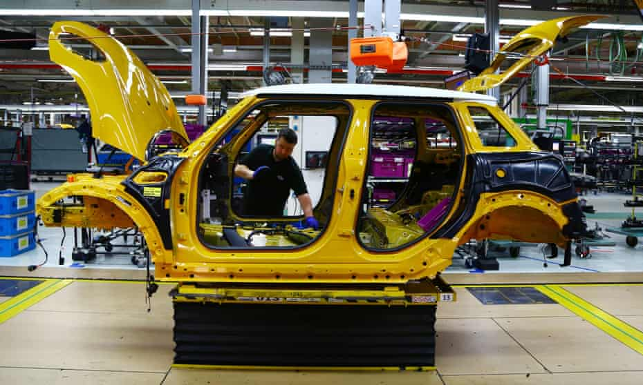 An employee installs a wiring loom into a Mini car as it travels along the assembly line at the BMW Mini car production plant in Oxford