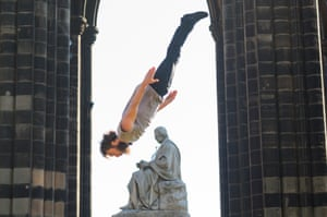 Circus performer Manu Tiger jumps over the Scott Monument in Princes Street during the festival fringe, Edinburgh