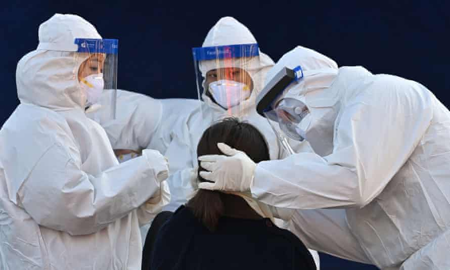 Medical staff carry out a coronavirus test outside Seoul station on Monday.