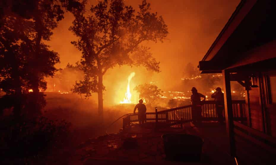 Firefighters watch flames from the LNU Lightning Complex fires approach a home in Napa County, California, in August 2020.