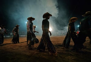 Monte Negro, south of the Amazon basin, Rondonia state, cowboys display their talent at a rodeo by riding bulls for as many seconds as they can