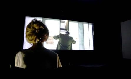 A woman views a video piece by Naeem Mohaiemen at Tate Britain
