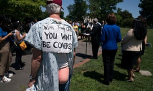 A demonstrator listens as Senate Democrats hold a press conference in opposition to the Republican bill.