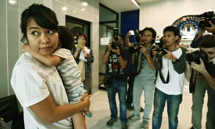 Noppawan Bunluesilp arrives at a police station in Bangkok with her three-year-old son.