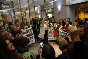 Activists from the NGO Non violent action COP21 sing and dance during a concert in a BNP Paribas bank