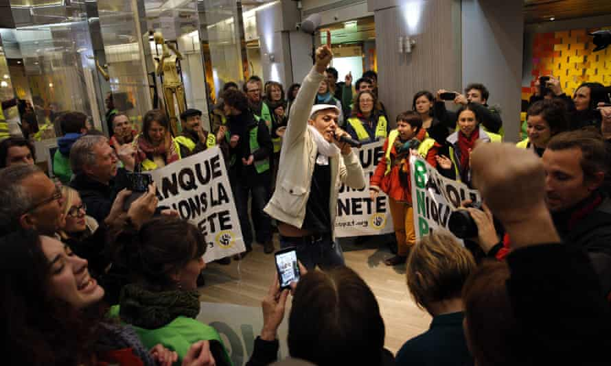 Activists sing and dance during a concert in a BNP Paribas bank they occupied in Paris on 9 Dec during the climate summit