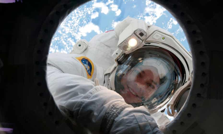 astronaut in bubble helmet peers into the ISS