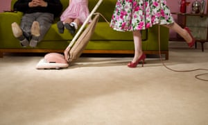 Housewife vacuuming under family's feet