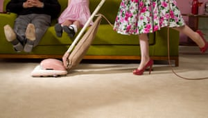1950s housewife hoovers under feet of family sitting on sofa