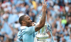 raheem sterling holds the FA Cup trophy after the Manchester City's victory over Watford