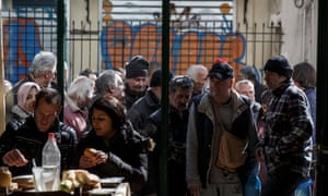 Greek people queue to enter a soup kitchen run by the Orthodox church in Athens.