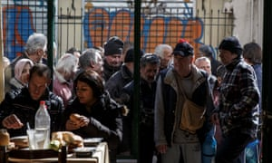 People queue to enter a soup kitchen run by the Orthodox church in Athens