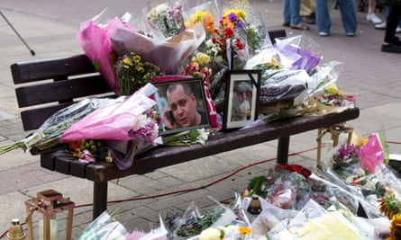 Floral tributes and a photograph of Arkadiusz Jóźwik are seen on a bench in Harlow, Essex